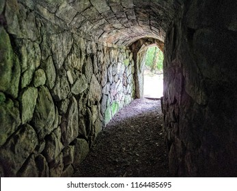 Tunnel constructed of stone blocks leading out to and exit where light can be seen.