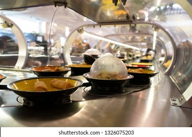 In the tunnel of conveyor belt of revolving sushi bar. You can eat what you want on the belt.