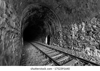 Tunnel on old shut down railway branch line between Oberbruegge and Halver Germany with brick wall Portal in green natural landscape of rural Sauerland. Black and white atmosphere at tunnel entrance