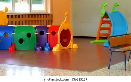 a tunnel shape game and a slide in the large hall of kindergarten without people