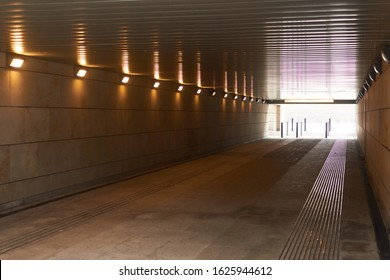 Tunnel, underpass with burning lamps and light at the end.