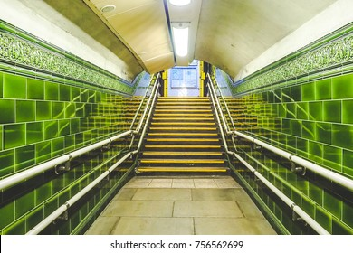 A tunnel's walkway in London Tube or underground with a green bricks wall and way out to the road.