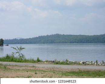 Tupper Lake, NY/USA - July 1, 2018:  Gentle ripples roll along the shoreline of Tupper Lake, with the Adirondack Mountains in the background.