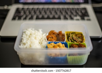 Tupperware with food in flont of computer
