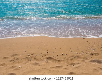 tuquoise blue sea water surface edge on sand beach with pebbles, sumer holiday natural background