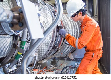 Turbine engineer wearing personal protective equipment and holding log book inspecting gas turbine engine at oil and gas central processing platform.