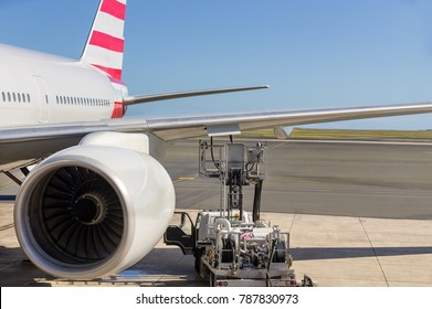 Turbo engine on a commercial airliner parked on the apron at an aerodrome with a motorised platform parked under the wing refuelling the tanks