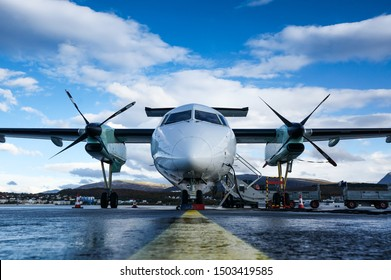 Turboprop passenger airplane captured from font uprisen angle parking at the airport