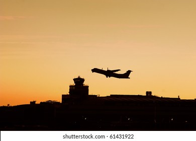 Turboprop plane flying over the airport tower in sunrise