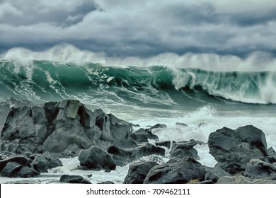 turbulent hurricane waves of Pacific ocean and rugged beauty of basalt rocks. Dangerous reefs as cay cavity