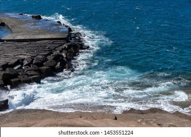 turbulent waves of the ocean break into a trail of stone and sand