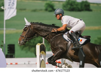 TURDA, CLUJ, ROMANIA - June 29, 2017: Unidentified competitor jumps with his horse above barriers at the Salina Equines Horse Trophy , June 29, 2017 in Turda, Cluj, Romania
