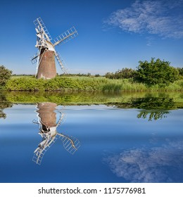 Turf Fen Windmill reflecting in the smooth waters of the Norfolk Broads, Norfolk, England