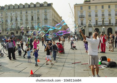Turin, IT - Circa Sep 2012 - Street artist creates giant bubbles to amuse children and tourists.