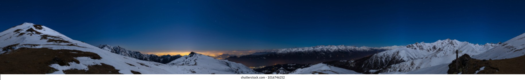 Turin city lights, night view from snow covered Alps by moonlight. Moon and Orion constellation, clear sky, 360 degree panorama. Italy.