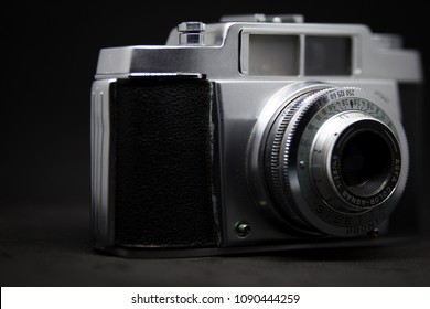 Turin / Italy - 05/12/2018: Old camera from the 70s, black body and silver finish, positioned on a black background