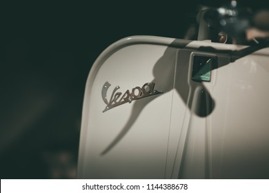 Turin/ Italy - 07/28/2018: The body of a Piaggio Vespa scooter from the 50s, white on a black background, with the shadow of the handlebars that sits on the historic Vespa logo