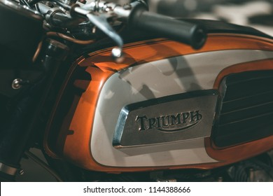 Turin/ Italy - 07/28/2018: The tank of an American Triumph motorcycle, with orange stripes and colored beige, focusing on the Triumph logo in metal on a vintage plate