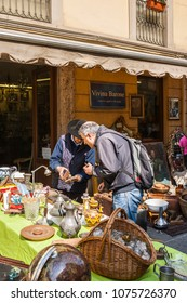 """Turin, Italy - April 16, 2011: Antiques shop in the """"Balon"""", the typical flea market of Turin, with seller and customer."""