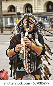 Turin, Italy - April 27, 2013: Red indian in traditional costume plays in the center of Turin, Italy. Street performance of a group of Native Americans with sounds and traditional dancing.
