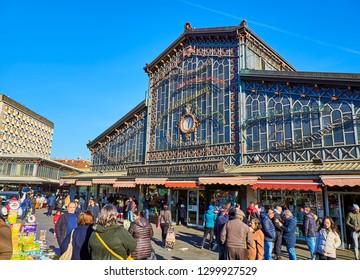 Turin, Italy - December 31, 2018. Citizens in front of the Antica Tettoia dell'Orologio building, the Fresh food part of Porta Palazzo market. View from the Piazza della Repubblica square. Turin.
