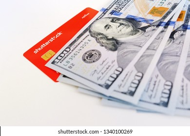 Turin, Italy - February 22, 2019: Payoneer card for Shutterstock and hundred dollar bills on white background