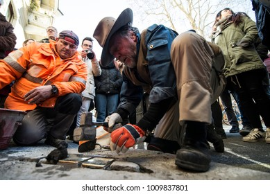 TURIN, ITALY - JANUARY 18, 2018: Artist Gunter Demnig lays one of his stumbling blocks at the 'Memory Blocks' performance in Turin, Italy. He started  in 1996 to remember the victims of Nazism.