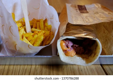 Turin, Italy - March 31, 2019: fries and Piada (thin Italian flatbread) filled with meat, cheese and vegetables at Eataly restaurant