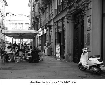 Turin, Italy - May 11, 2018.  Historic center, just before Piazza Castello. Italian cafe, tourists. Black and white photo.