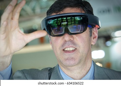 Turin, Italy - May 5, 2017: Young man wearing virtual reality headset or goggles looking around and trying to touch something
