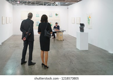 TURIN, ITALY - NOVEMBER 2018: an elegant couple of collectors look at the works at the contemporary art fair