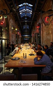 TURIN, ITALY - NOVEMBER 3, 2018: Ogr, Officine Grandi Riparazioni cafe interior with people, evening in Turin, Italy.