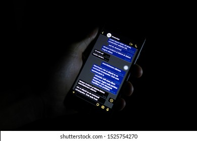 Turin, ITALY- October 10, 2019: Person holding a phone displaying a possible look of the dark mode of WhatApp, the popular message application.