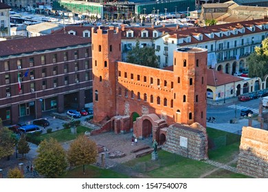 Turin, Italy - October 26, 2019: The Palatine gate  is a Roman Age city gate located in Turin, Italy. Sunset view from the cathedral bell tower in autumn.