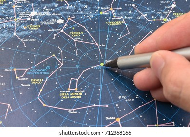 TURIN, ITALY, SEPTEMBER 2017: a female caucasian hand shows with a silver pencil the Pole or Polar star of the Ursa Minor constellation on an Italian sky map.