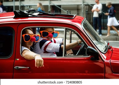 TURIN, ITALY - SEPTEMBER 24, 2017 - Funny looking couple driving an old red Fiat 500 during a classic car rally in Turin (Italy) on september 24, 2017