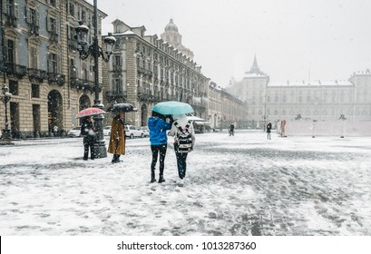 Turin italy in winter, tourist with umbrella in the main square under heavy snow storm