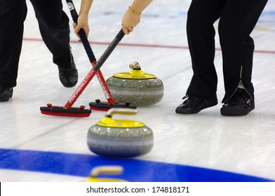 TURIN, ITALY-FEBRUARY 19, 2006: Close up of Curling stones sliding on ice during the Winter Olympic Games of Turin 2006.