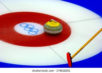 TURIN, ITALY-FEBRUARY 19, 2006: Close up of Curling stone on red traget during the Winter Olympic Games of Turin 2006.