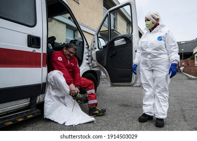 TURIN, ITALY-MARCH 25, 2020: Red Cross personnel in protective containment suits prepare to go out with an ambulance for covid 19 patient transportation on Hospital