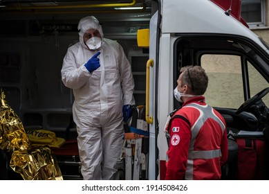 TURIN, ITALY-MARCH 25, 2020: Red Cross personnel in protective containment suits prepare to go out with an ambulance for covid 19 patient transportation on Hospital.