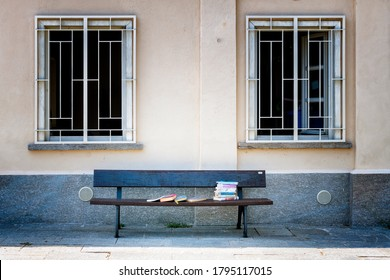"Turin, Piedmont, Italy - August 12, 2020: Mausoleum of ""Bela Rosin"", public library in Turin. Detail of the external facade with a wooden bench and books placed on top"