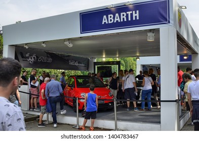 Turin, Piedmont, Italy. June 2018. At the Valentino park, the motor show. The abarth stand is crowded with people, a boy is still in front of the 500 model to admire it.