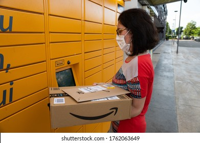 Turin, Piemonte, Italy. June 2020. A Caucasian woman is picking up her shipment at an amazon locker. He holds the packaging with the logo in his hand and reads the communications on the screen.