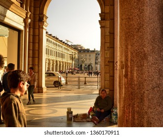 Turin, Piemonte, Italy. March 2019. In the arcades along Via Roma, beggars and tramps are often found, a child curiously looks at a woman sitting on the ground.