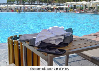 Turkey Antalya Belek, 21 July 2019: detail close up of summer clothing and smartphone on wooden table with hotel swimming pool blue water in background