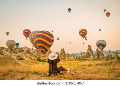 Turkey balloons Cappadocia Goreme Kapadokya , Sunrise in the mountains of Capadocia, young woman watching sunrise