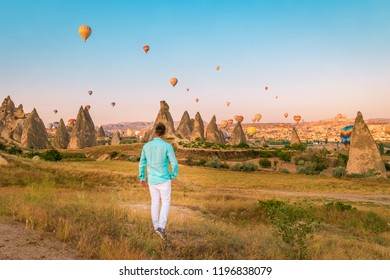 Turkey balloons Cappadocia Goreme Kapadokya , Sunrise in the mountains of Capadocia, happy young man watching sunrise