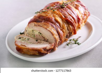 Turkey breast roll with herb cheese, wrapped in bacon rashers