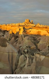 Turkey. Cappadocia. View on rock-castle of Uchisar town across a Guyercinlik valley at a sunrise